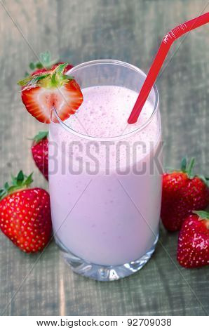 Strawberry milk shake with strawberries on wooden background soft focus on strawberry on the glass