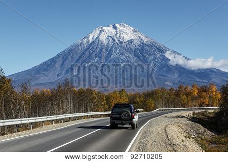 Car Goes On The Road To Koryaksky Volcano On Kamchatka. Russia, Far East