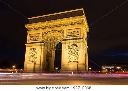 Illuminated Arc De Triomphe With Light Rails Of Passing Traffic In Paris