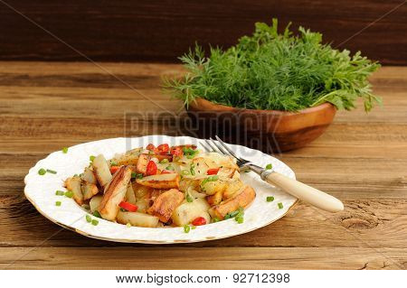 Fried Potatoes With Scallion And Chili In White Plate With Fork And Fresh Herbs In Wooden Bowl