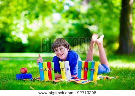 Student Boy Relaxing In School Yard Reading Books