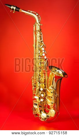 Alto saxophone in full length on red background