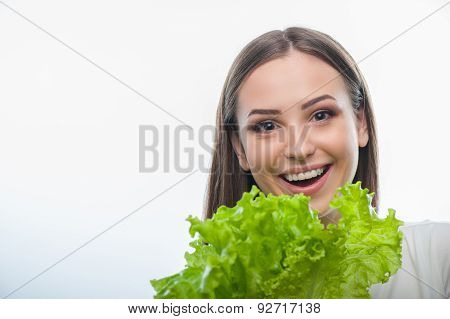 Pretty healthy woman is standing with green vegetable