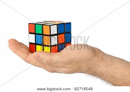 MOSCOW, RUSSIA - January 07, 2015: Hand and Rubik's cube puzzle isolated on the white background. Cube was invented by a Hungarian architect Erno Rubik in 1974.