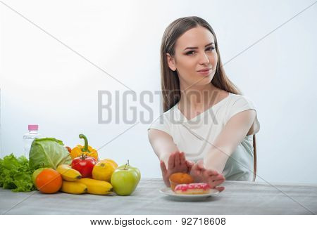 Beautiful young woman is refusing to eat unhealthy food
