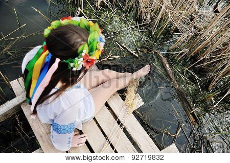Girl Wets Feet In The River. Girl Sitting On The Bridge In The Ukrainian Shirt And A Wreath Of Flowe
