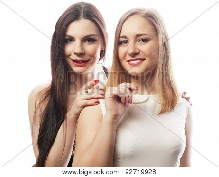 Two young girl friends standing together and looking at camera. Over white background.