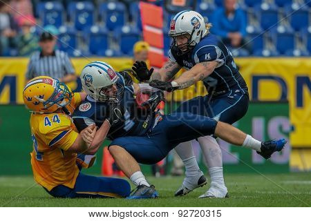 ST. POELTEN, AUSTRIA - JUNE 1, 2014: QB Miro Kadmiry (#7 Finland) is tackled by DL John Lannefors (#44 Sweden).