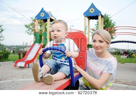 Mom And Baby Son Play In The Playground