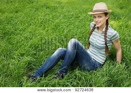 Young Girl Sitting On A Grass