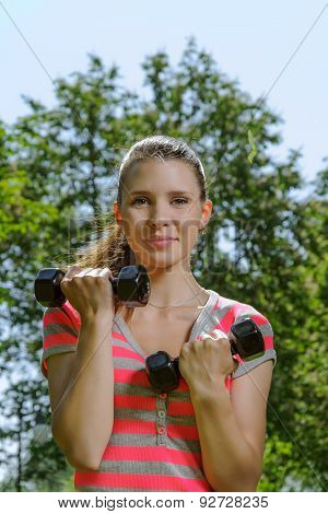 Fitness Female Performs Exercises With Lightweight Dumbbells