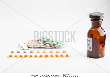 Bottle with pills on white