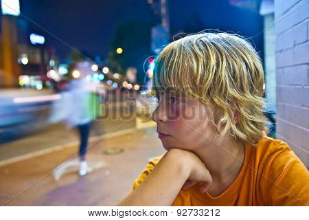 Cute Boy Smiles Tired While Sitting Outside By Night