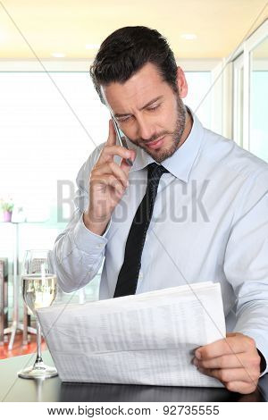 Businessman With Mobile Reading The Newspaper, Paused At The Bar With A Glass Of Wine