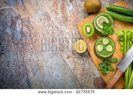 Green smoothie,cucumber,lemon,kiwi and celery on stone background
