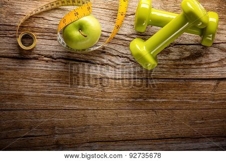 Two dumbbells,green apple, measuring tape on wooden background
