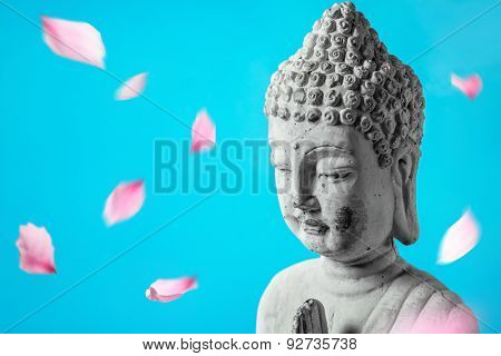 Buddha in meditation with flower petals