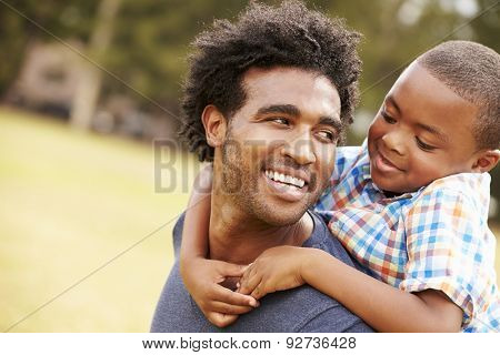Father Giving Son Piggyback Ride In Park