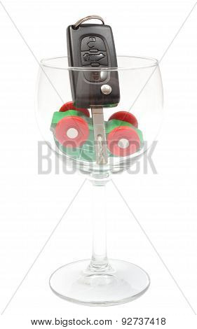 Overturned Model Vehicle And Car Key In Glass Of Wine. White Background