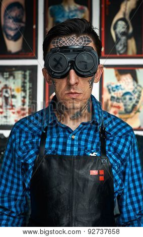 Tattooed Man In Welder Glasses And Shirt