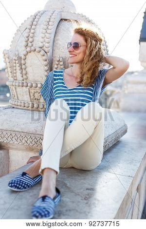 Woman With Curly Hair Sitting On Bridge