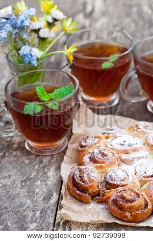 Homemade Cinnamon Buns With Tea Cups And Bunch Of Wild Flowers