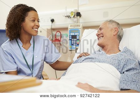 Nurse Sitting By Male Patient's Bed In Hospital