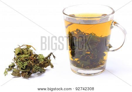 Dried Nettle And Cup Of Beverage On White Background