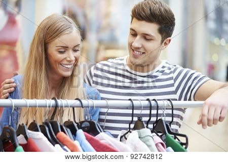 Couple Looking At Clothes On Rail In Shopping Mall