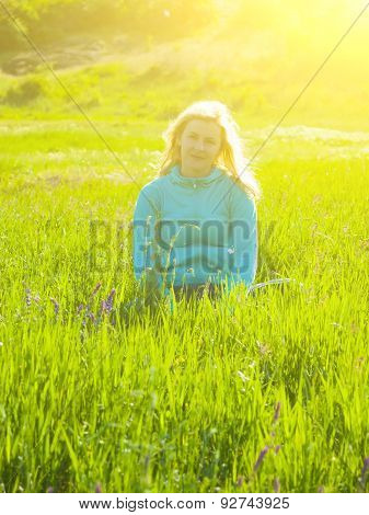 Girl Sitting In A Field On The Green Grass.