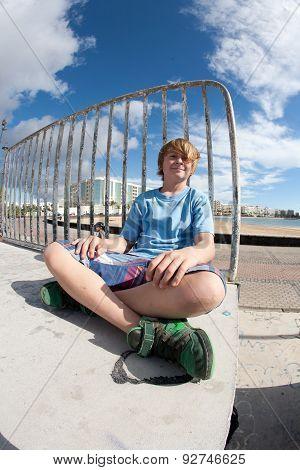 Cute Boy Sitting At The Skate Park