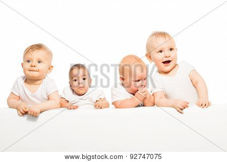 Cute babies stand in a row on the white background