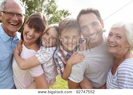 Multi Generation Family Giving Children Piggybacks Outdoors