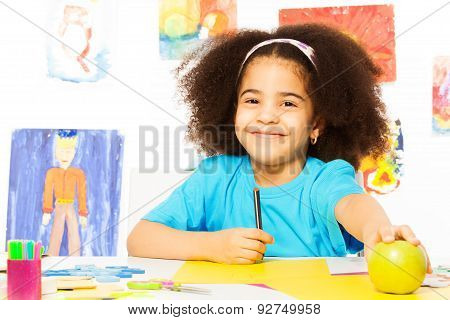 Smiling African girl holds pencil and apple