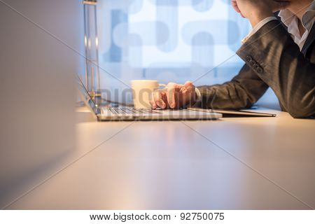 Businessman Using Laptop With Coffee On The Side