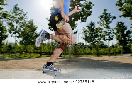Close Up Athletic Legs Of Young Man Running In City Park With Trees On Summer Training Session Pract