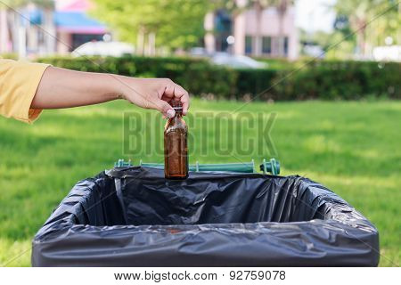 Hand Throwing Empty Glass Bottle Into The Trash