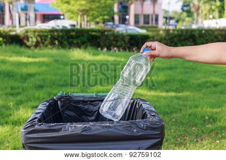 Hand Throwing Empty Plastic Bottle Into The Trash