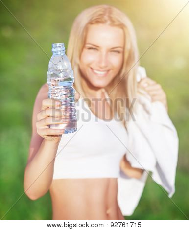 Selective focus on a woman holding bottle of water, doing sport exercise outdoors, healthy nutrition, enjoying fitness life