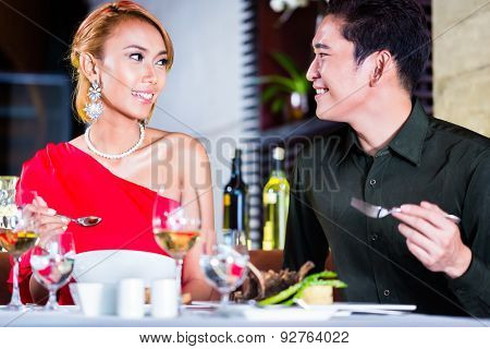Asian couple fine dining in fancy restaurant