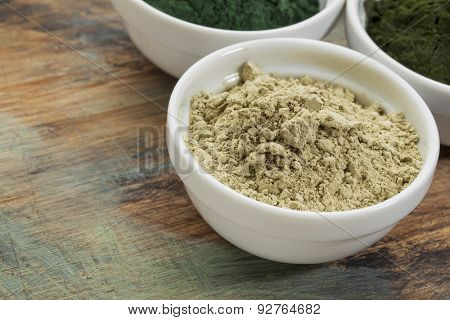 a bowl of kelp seaweed powder with spirulina and chlorella in background