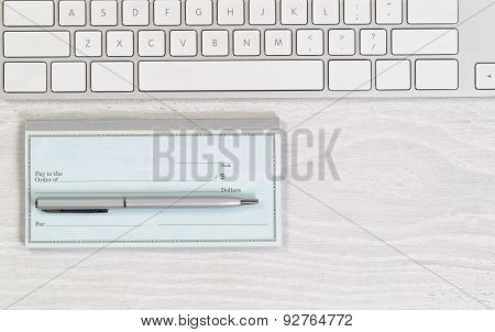 Blank Checkbook With Pen On White Desktop