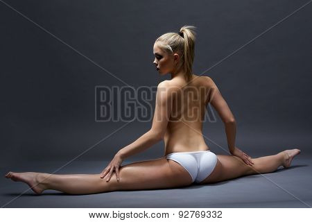 Rear view of topless girl doing gymnastic split