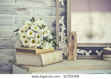 Wedding Bouquet Of Daisies On A Stack Of Books