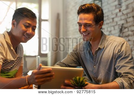 Two Men Using Tablet Computer at Table Cafe, Friends Guys Sitting