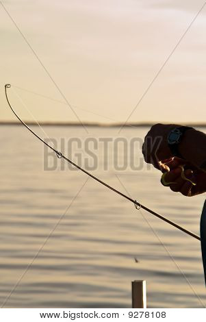 A Silhouette Of A Man's Hands And Fishing Rod Against Water