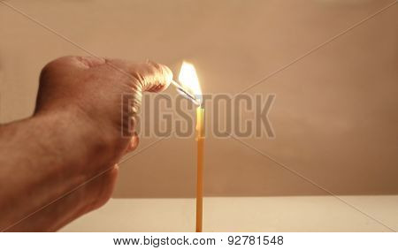 Hand With A Match And A Candle