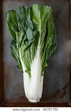 Bok choy still life on a used metal baking sheet. Vertical format.