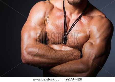 Muscular and sexy torso of young sporty man showing his perfect bicep, shoulders, chest. Torso part.