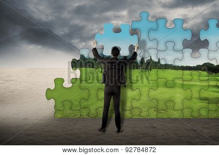 Business Man Assemble Puzzle To Change From Desert To Landscape